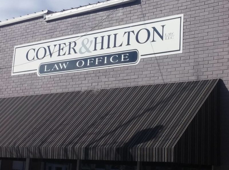 Cover and Hilton Law sign